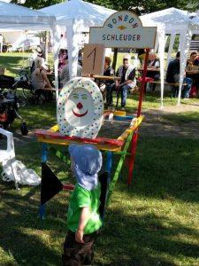 Ein Kind steht vor einer Bonbonwurfmaschine