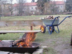 Lagerfeuer und Schubkarre mit Holz
