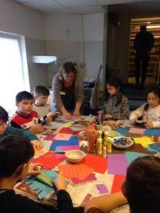 Ein Tisch von Kindern umrundet, eine Frau zeigt Origami