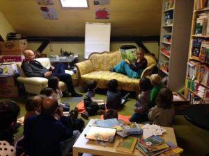 Eine Frau sitzt auf einem Sofa und liest Kindern vor